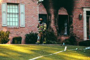 Fireman walking in front of house that caught on fire