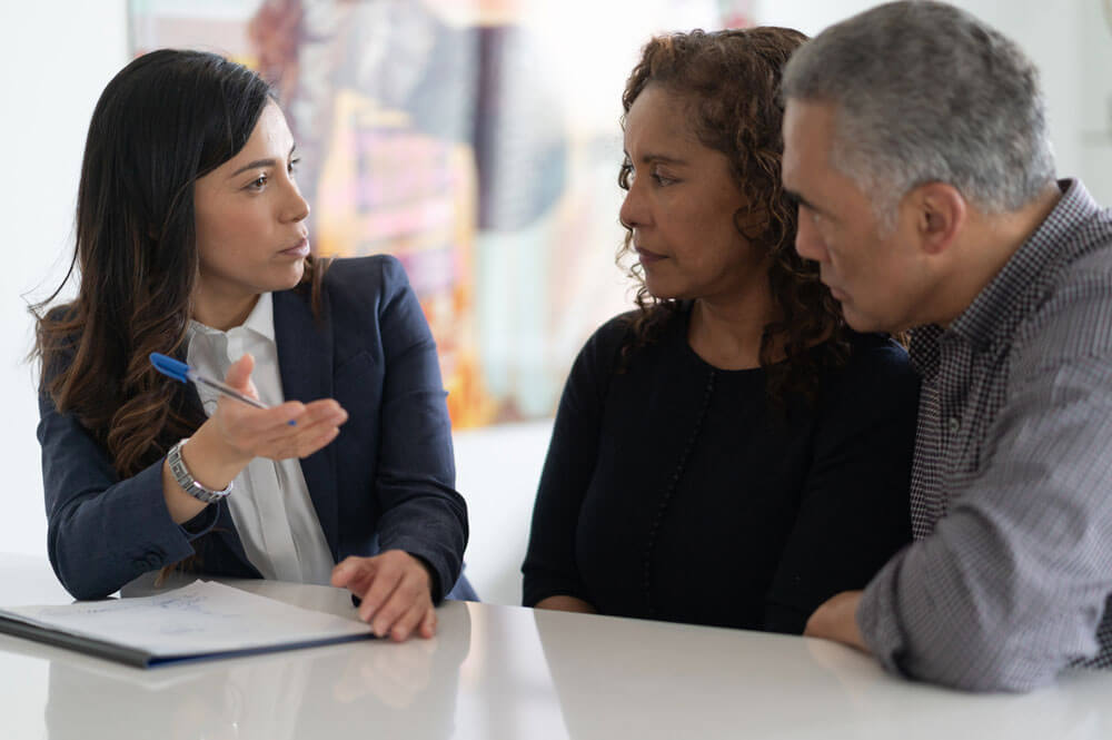 Insurance Agent Explaining Policy Options To Couple