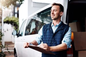 Man with clipboard in front of commercial van