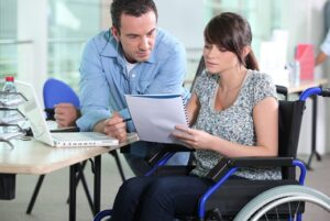 woman in wheelchair reviewing paperwork with man