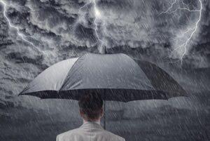 Man holding umbrella in rainstorm