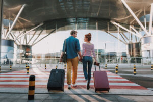 couple pulling luggage at airport