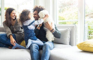 Family on couch with a dog